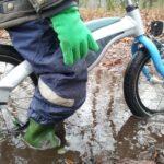 Jongetje op kinderfiets met regenkleding aan, Ouders van Nature.nl