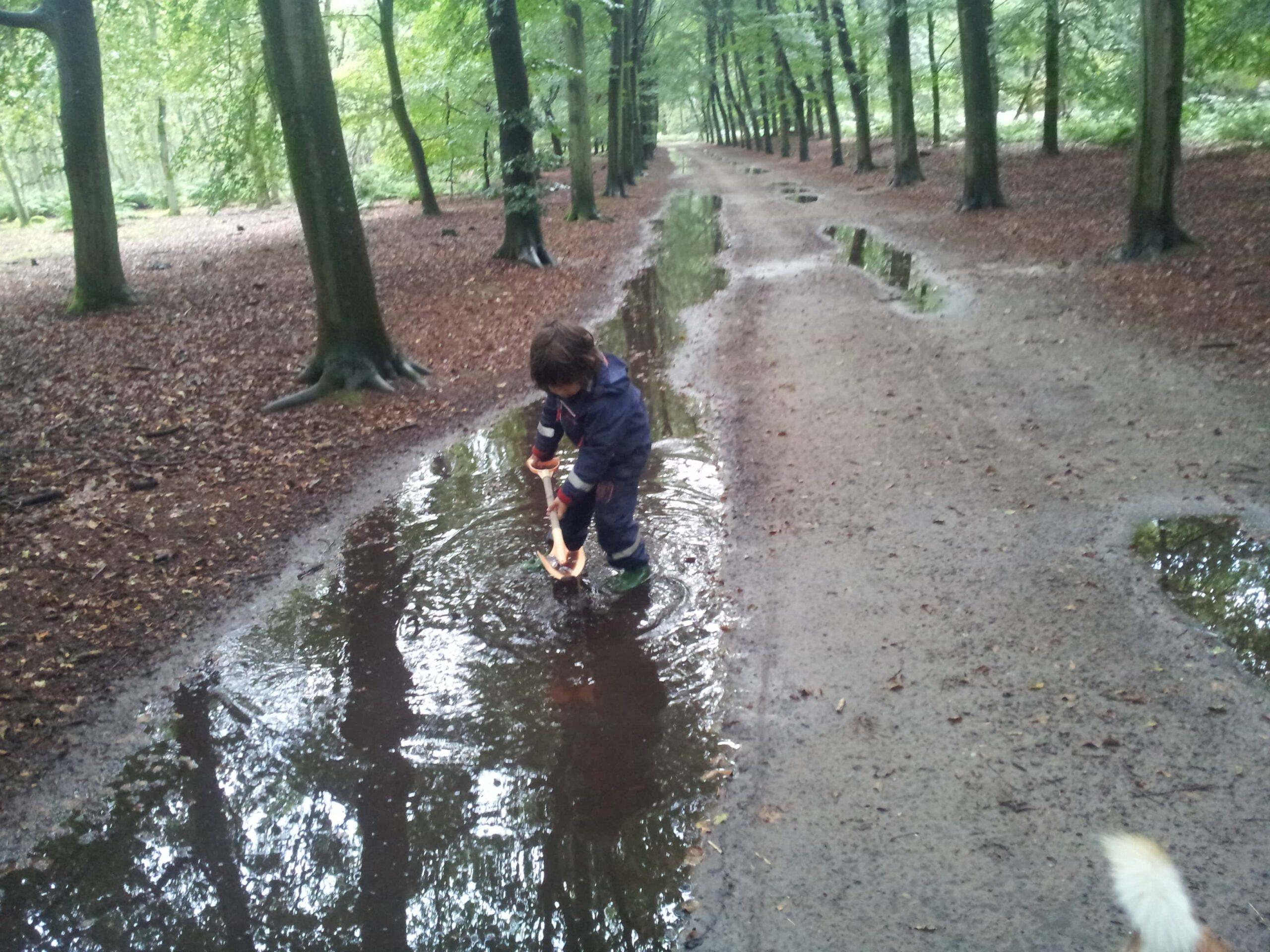 Zoontje speelt in de plassen