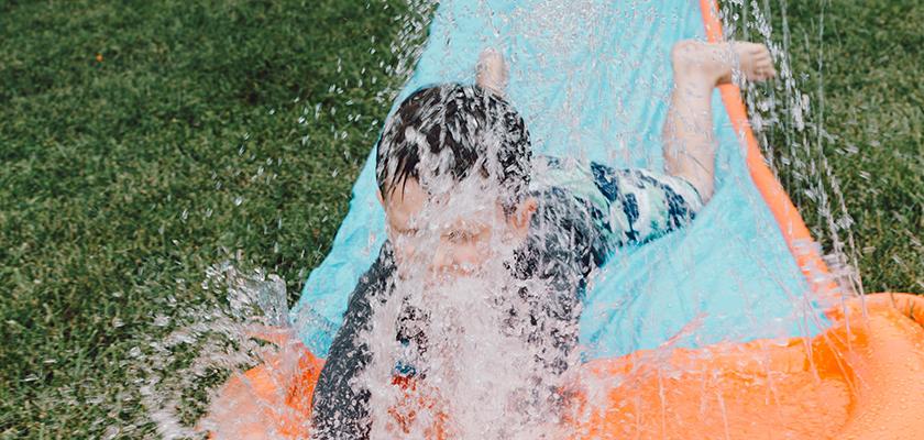 Spelen met een waterglijbaan is fijn als het warm is.