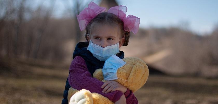 Kinderen kunnen erg bang zijn voor het coronavirus zoals dit meisje met mondmaster en teddybeer.